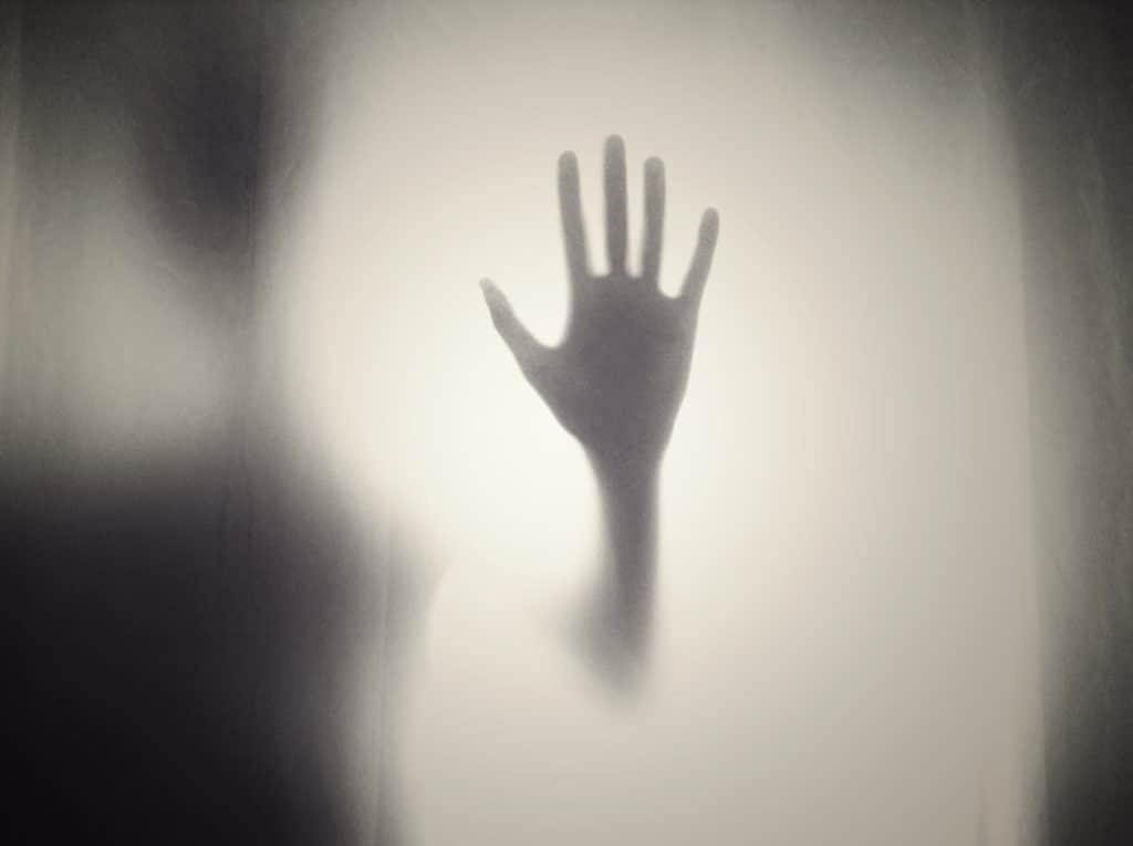 Creepy hand on fogged glass