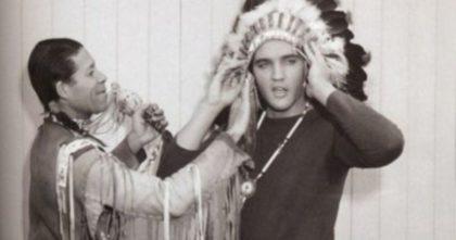 Elvis Presley wearing a Native American headdress.