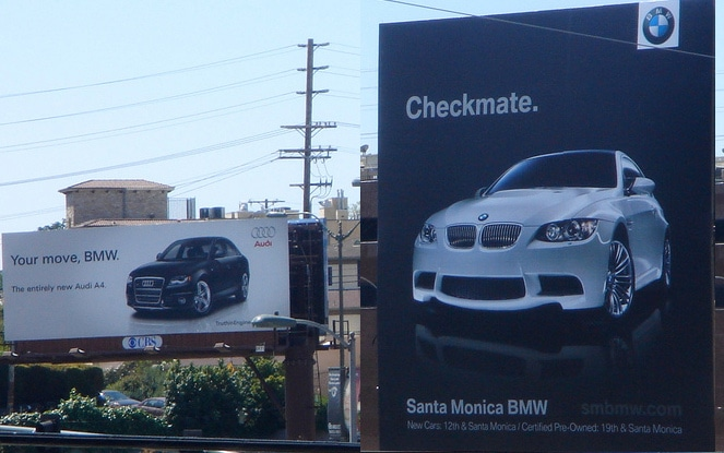 Two billboards for car companies with a competitive rivalry.