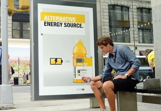 A clever ad for energy drink Vitaminwater at a bus shelter, allowing a man to charge his phone.