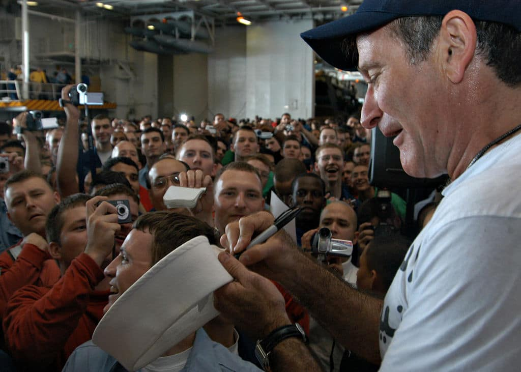 Robin Williams signing a marine's cap