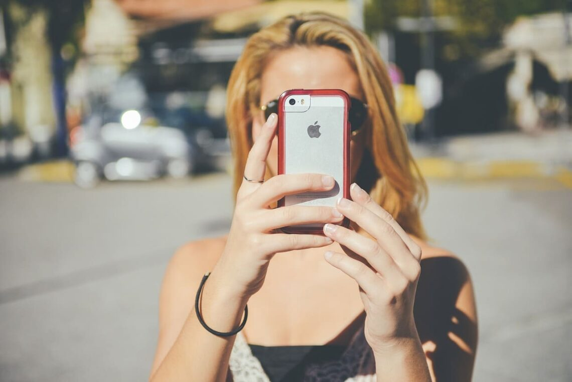 A young woman holding an iPhone in front of her face