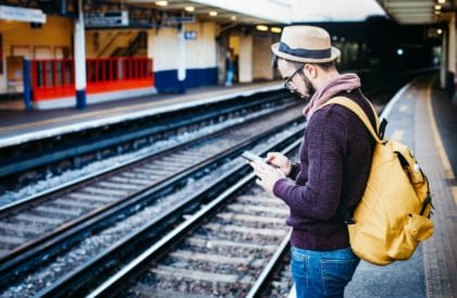 Man checking emails at train station