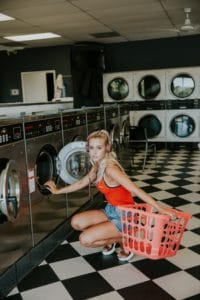 Woman listening to podcasts with headphones while doing laundry
