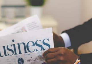 Man in suit reading business newspaper
