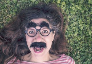 A laughing woman wearing a false nose, glasses, mustache, and bushy eyebrows for comedic effect