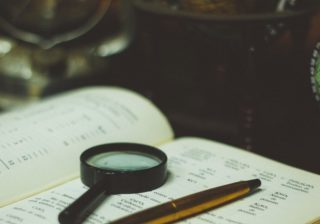 A detective's magnifying glass lying on an open book