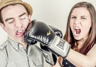 A rivalry in which a man is being punched by a shouting woman in boxing gloves