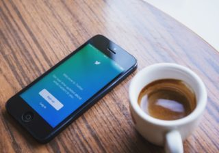 The twitter app open on a cellphone, beside a cup of coffee