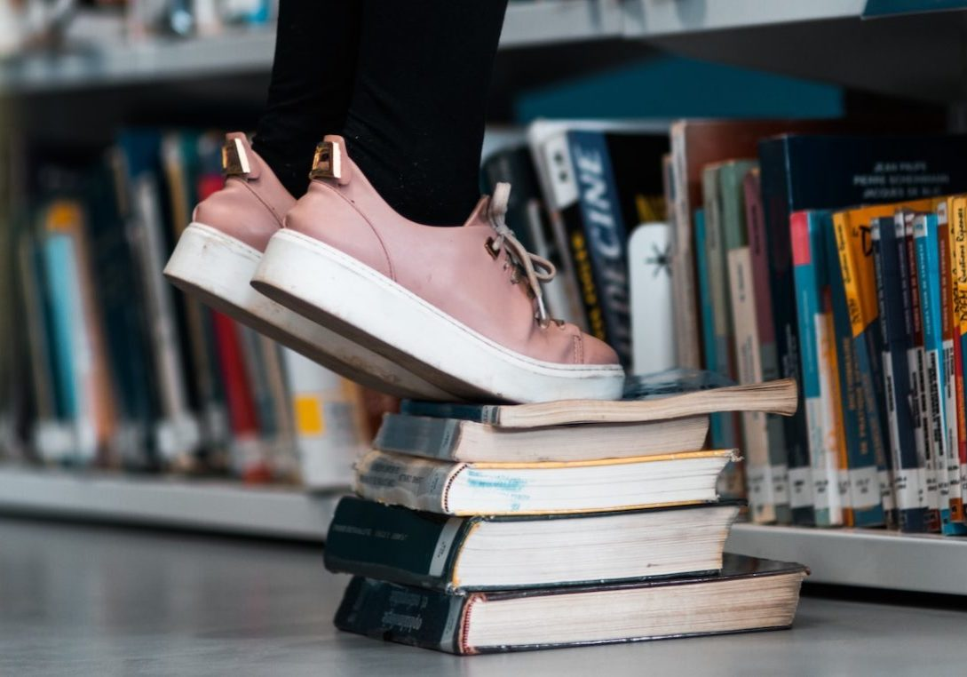 image of person standing on books next to bookcase representing research