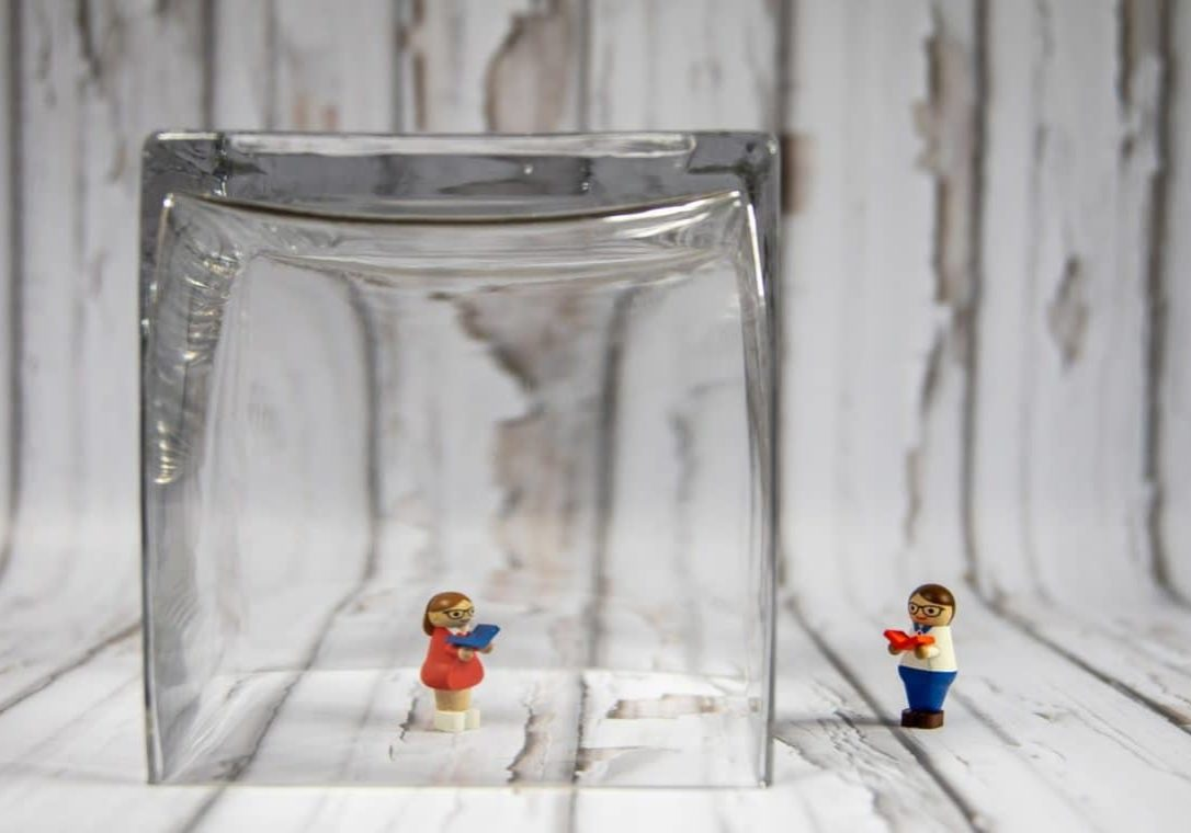 image of toy figures separated by glass representing social distancing due to coronavirus