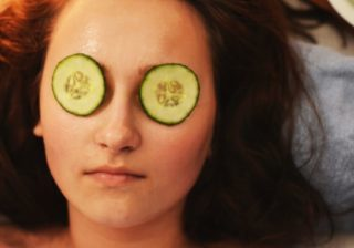 A woman relaxing in a spa with cucumbers on her eyes